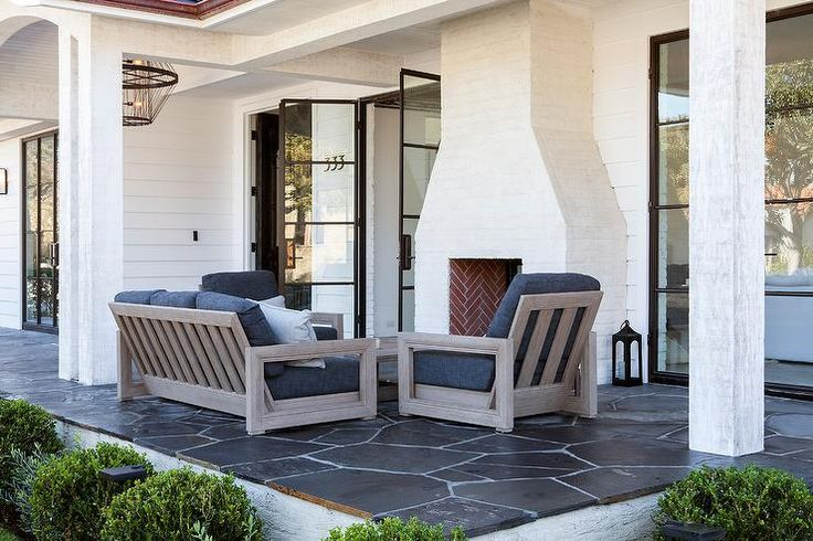 A gray teak sofa topped with a charcoal gray cushions sits on a covered patio flanked by matching chairs placed facing a gray teak coffee table warmed by a white brick fireplace accented with a red brick firebox.