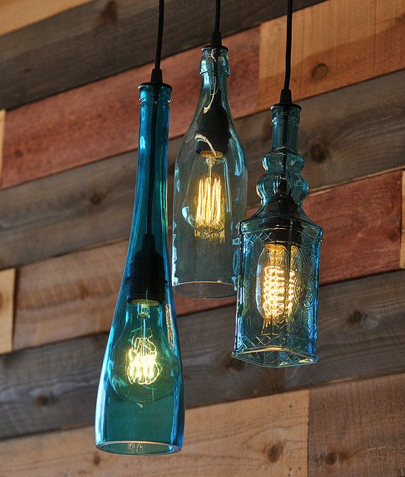 This is a pendant chandelier made from 3 recycled teal colored bottles. They hang from an 8 brass canopy that can be finished in black, oil rubbed