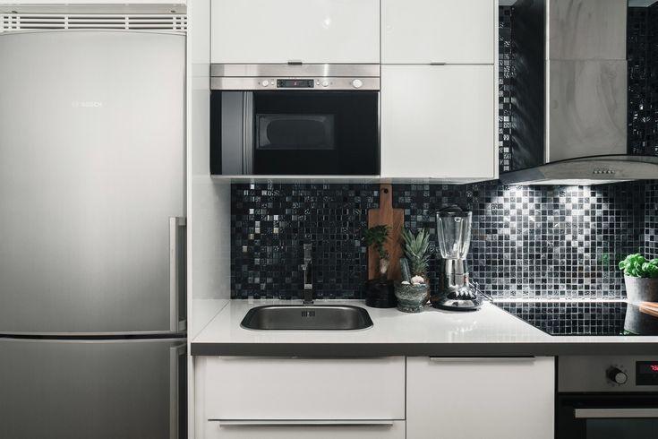 Кухня достаточно компактная, поэтому над кухонной раковиной расположилась микроволновка.