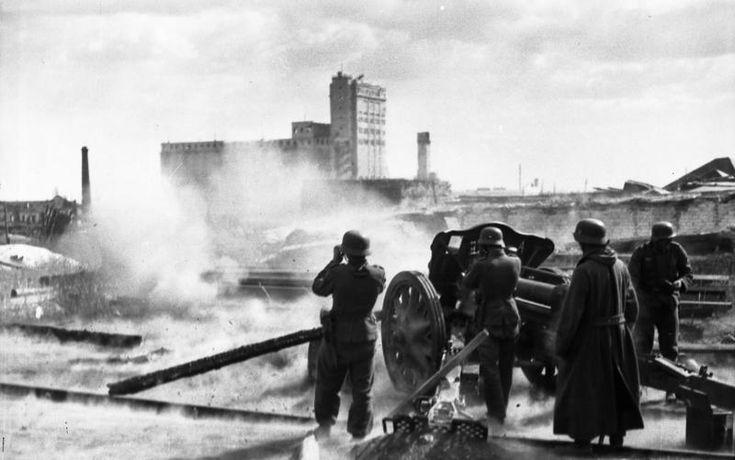 German 10,5 cm leFH 18 disparos, con el elevador de granos Stalingrado en la distancia. Bundesarchiv