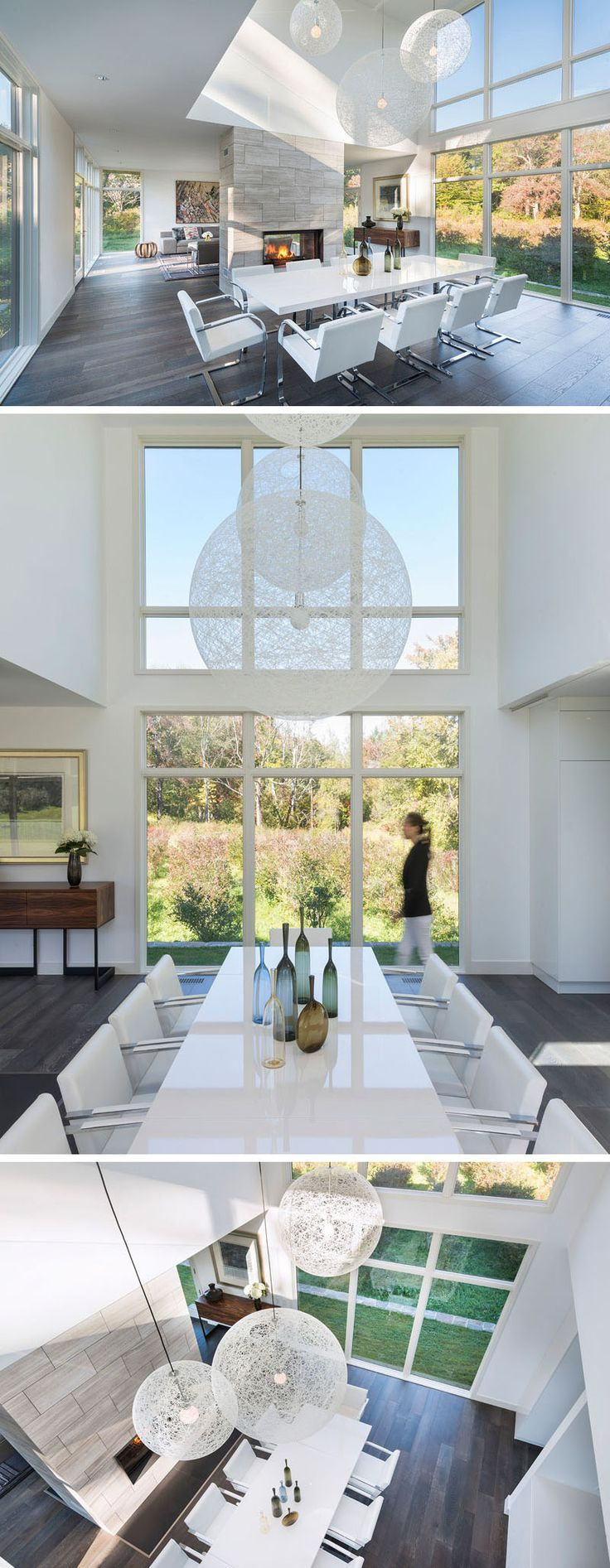 In this modern dining area, three large white pendant lights hang from the double height ceiling in front of floor-to-ceiling windows. A light grey tiled fireplace behind the white dining table separate this space from the living room.