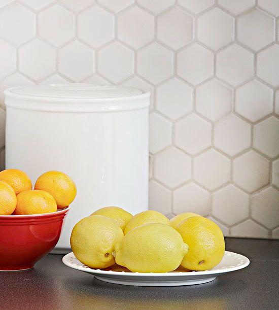 Backsplash Beautification Petite 2x2-inch gray hexagonal matte backsplash tile complements the black countertops.