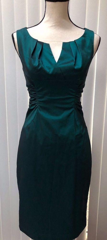 "Chic cocktail dress in emerald green satin finish poly/spandex. Center back zipper, back hemline slit. Fully lined. Surplice bodice with V neck, straight skirt, side ruching at waistline. Chest 34"". 