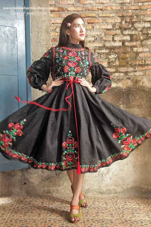 Batik Amarillis made in Indonesia  Batik Amarillis's Ildiko dress  in beautiful  & extravagant Hungarian embroidery this 70ies inspired dress  oozing romanticism with this full circle  skirt,beautiful puff sleeves , tassel belt and each details lends the style an ethereal charm.