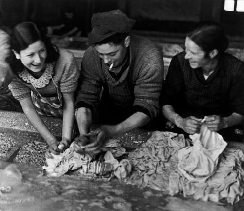 love-spain:    A Republican soldier helps the women with laundry for the troops; Madrid, Spain - November 1936.Photo by Robert Capa.Love-Spain