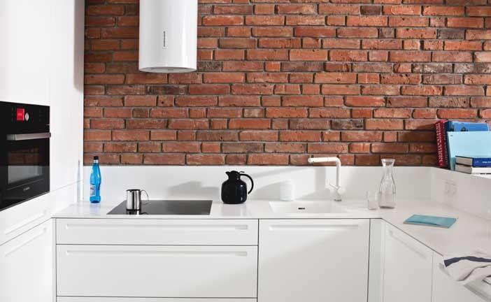 Fronty kuchni lakierowane na biały półmat, blat wykonany z 13 mm białego corianu oraz indywidualnie zaprojektowany odfrezowany uchwyt tworzą doskonale skomponowaną minimalistyczną formę