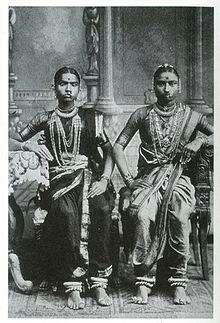 Una bayadera odevadasi(ensánscrito: 'sirvienta de dios') era una chica de laIndia del Surque estaba dedicada a servir y venerar a la deidad de untemplodurante toda su vida. Antes del dominio británico gozaban de un ambiguo rango social. Además de servir a la deidad, entretenían a los fieles con diversos procedimientos, entre ellos bailes sagrados como elbharatanatyam, además de ejercer la prostitución.  Durante elRaj británico, la tradición no podía perdurar. Solo en teoría ya no…