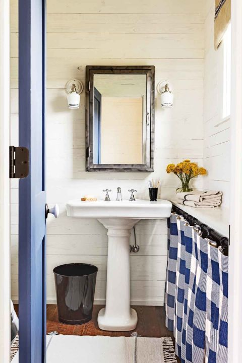 In this guest bathroom, designer Melanie Milner dressed windows with valances made from German feed sacks.