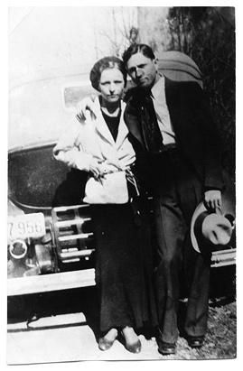 Bonnie Parker and Clyde Barrow stand next to each other behind a car in an undated photo.  ~  ; http://en.wikipedia.org/wiki/Bonnie_and_Clyde  ~  A&E ~  http://variety.com/2013/tv/news/lifetime-ae-history-to-simulcast-bonnie-clyde-1200616412/  ☚<<<Here's the links