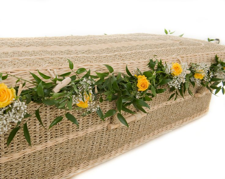 Flowers can be woven into the weave of our coffins to stunning effect, pictured here is our Pandanus Round adorned with flower garlands