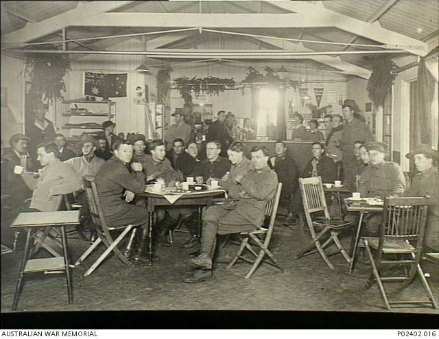 Interior of the canteen at No. 1 Australian Auxiliary Hospital (1AAH). Soldiers are seated at tables with cups of tea and smoking while others stand at the counter talking with the female staff. ...