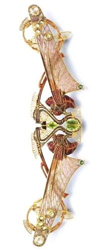 Lalique 1903 Corsage Ornament: an enamel & gold openwork hinged plaque, set w/2 oval-cut peridots, designed as two facing dragonflies, each w/ a brown enamel body & a cabochon ruby eye, extending pale orange plique-à-jour enamel wings w/gold scrolls & cabochon peridot accents, mounted in gold