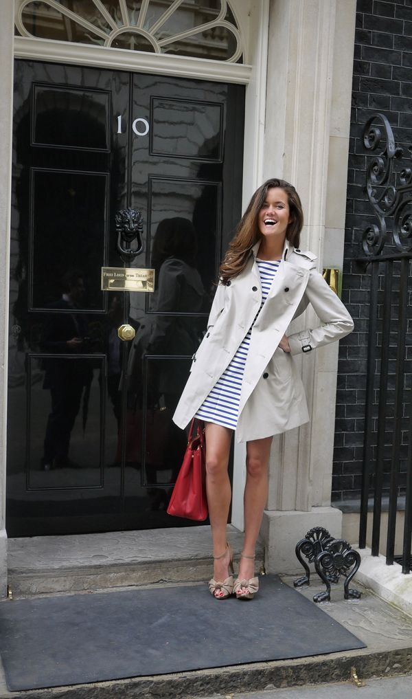 Striped dress layered under a trench coat with a bright bag.