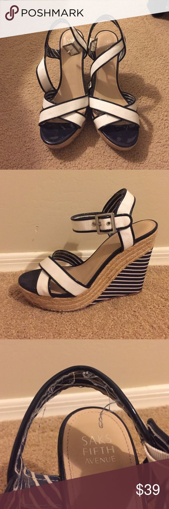 Saks Fifth Avenue Espadrille wedges Navy blue and white Espadrille wedges. I purchased them years ago but only wore them a couple times. The stitching on the fabric lining on the inside of the straps is shedding. (As pictured). I do have the original box if you are interested. Saks Fifth Avenue Shoes Espadrilles