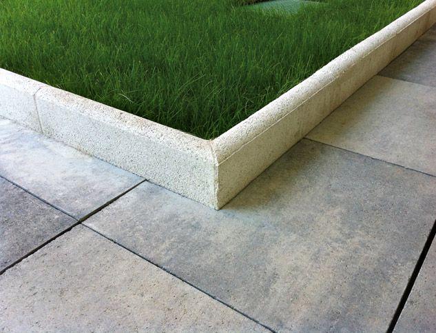 Patio delantero: bordillo de jardín de hormigón blanco de 50x20x6 cm delimitando las áreas situadas a ambos lados del paseo de acceso.