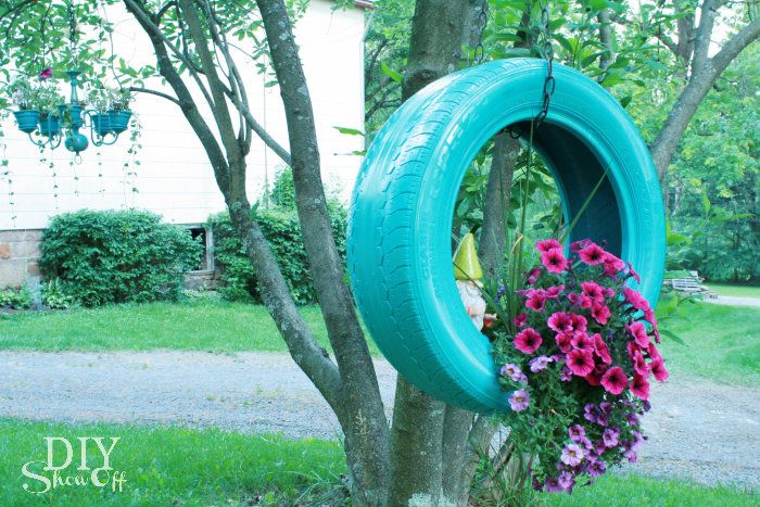 I like this planter hanging from a tree. On the wall, not so much. I'd love to see the tire in red with white petunias spilling out.
