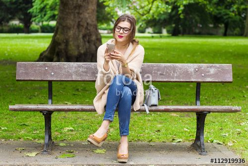 Cute young girl sitting on the bench and using smartphone in the park