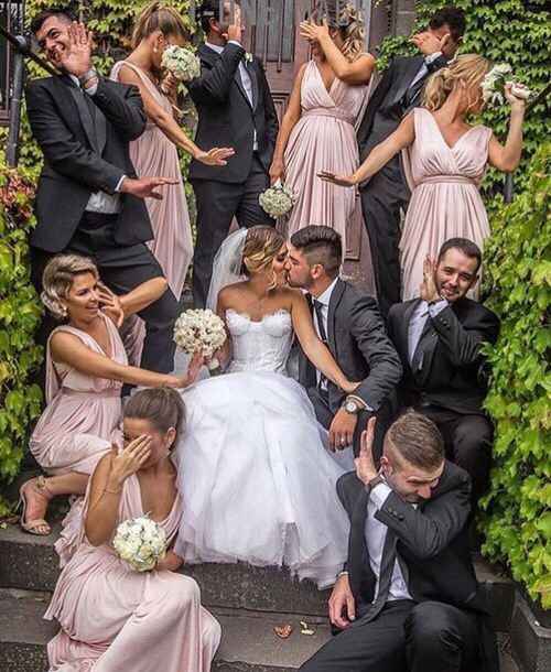 Love how funny this is and that there is so much going on.... different poses/levels/expressions and that they are all surrounding the bride and groom