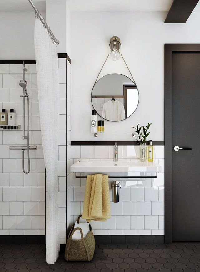 Sala de baño con paredes divididas horizontalmente entre cerámica y pintura, ambas blancas, las separa una franja negra. Sobre el lavamanos un espejo redondo con correa que cuelga desde el apliqué.