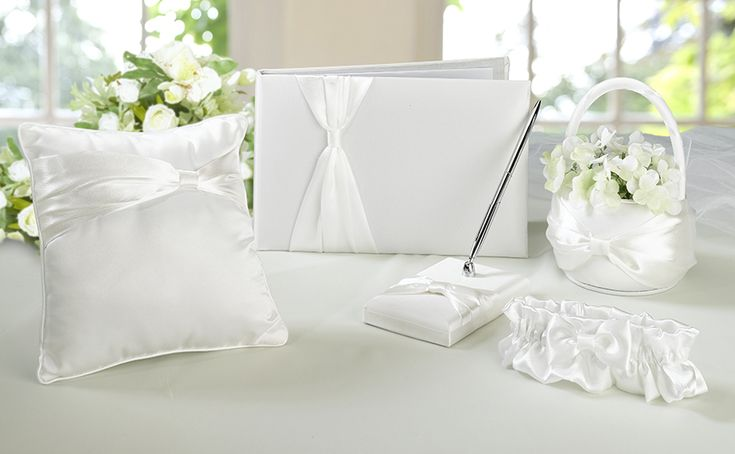 "-This cream satin wedding set includes 5 wedding accessories essential to completing your perfect day.  Included are the following items: one 10"" x 6.25"" guest book, one 3.5"" x 3.5"" pen set, one 7.5"" ring pillow, one 6.5"" x 4.5"" flower basket and one leg garter (one size fits most).    All accessories (except the garter) are decorated with a cream satin sash.  The garter is decorated with a cream satin bow."
