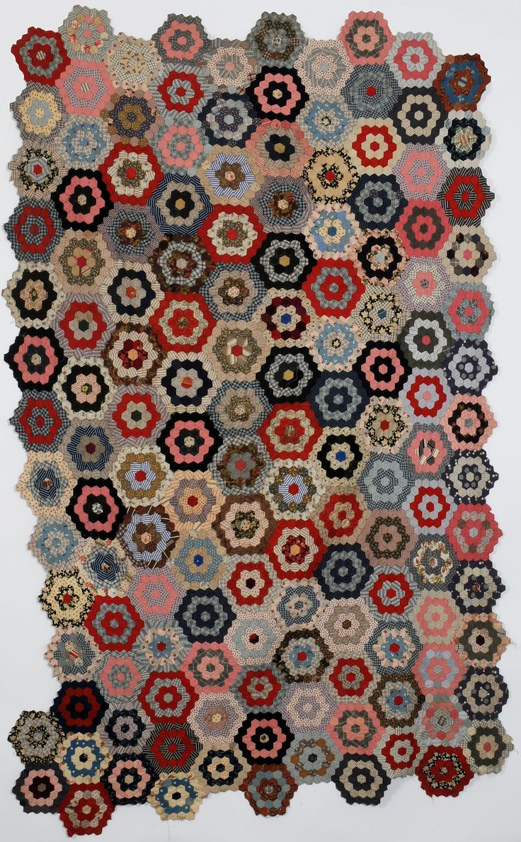 An unfinished late 19th century patchwork bedcover from Port Talbot, UK. Made from plain and printed cotton hexagons. The paper templates remain in parts. Lovely colors! I see this reproduced in French General fabrics.