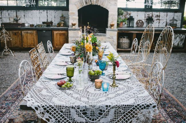 very boho! I love the lace tablecloth, and the colored glassware, coupled with mix-matched plates. the candleholders with flowers in them is also a great idea! nice reception table/ and or bride and groom table!