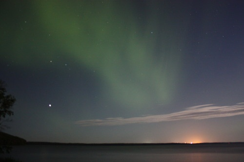 The Aurora Borealis over Gregoire Lake and the orange glow of Fort McMurray