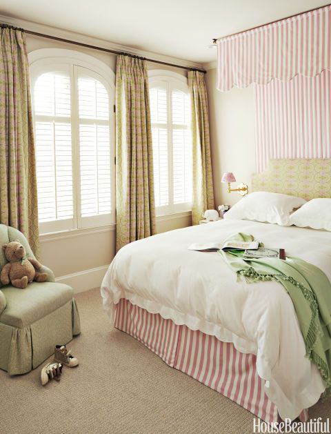 """""""The daughter's room is very feminine,"""" says Weiss, who used Pindler's Mayer stripe for the canopy and bed skirt, and Raoul Textiles' Amijao for the headboard and curtains."""