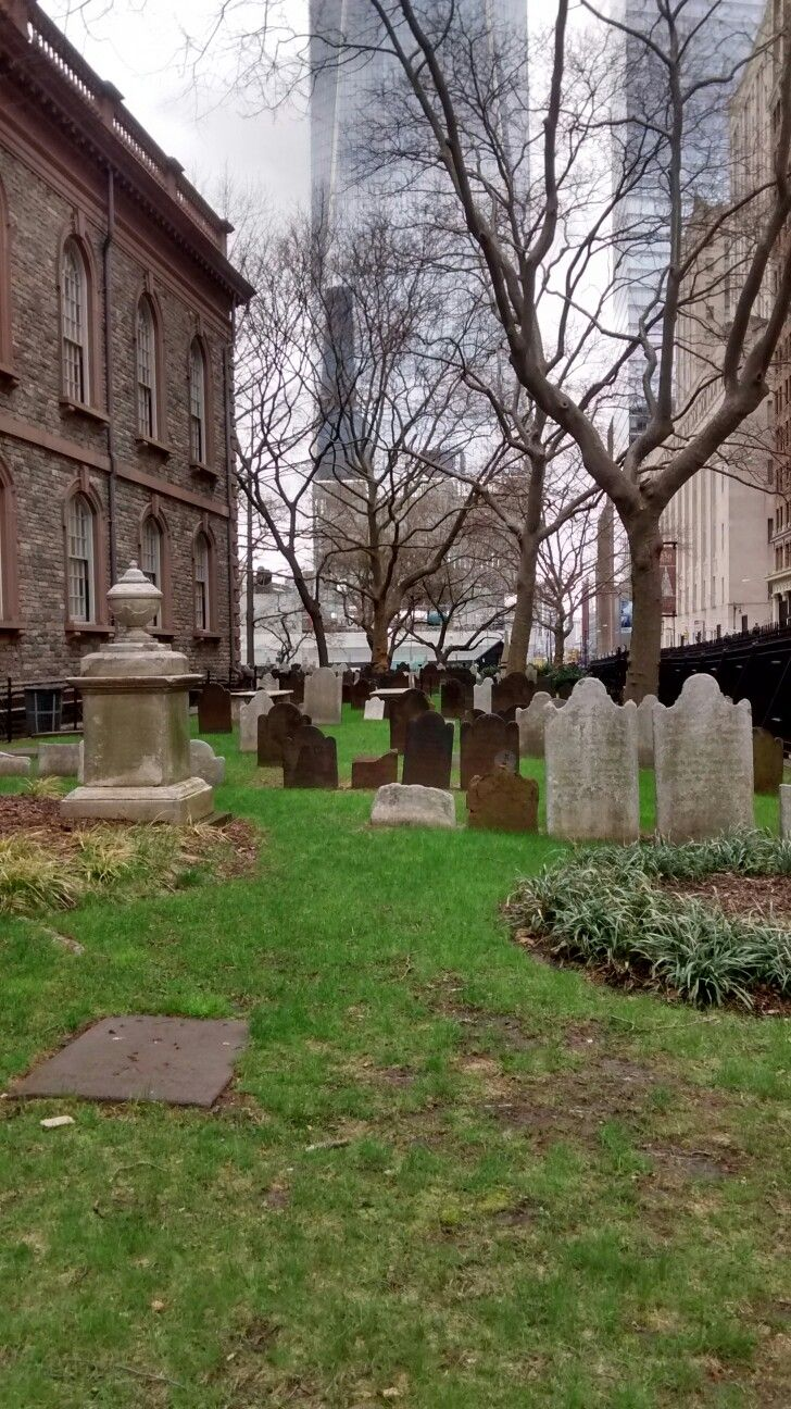 Graves of early Americans surround the St. Paul's Chapel; lower Manhattan.  One World Trade Center building in background.  April 2017.