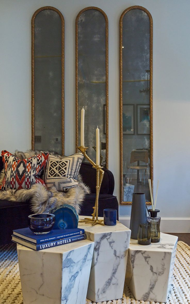 A trio of chic mirrors creates a spacious sense of grandeur in our living room design, whilst the characterful candle holder sits atop the trio of white faux marble coffee tables by Eichholtz adding artistic flair and personality to the scene.
