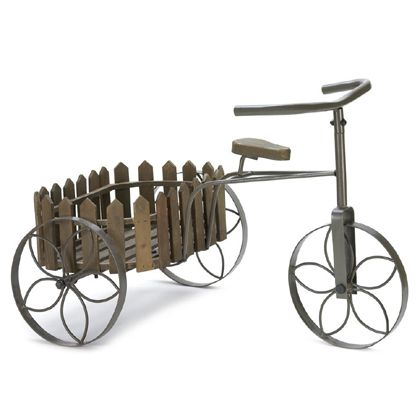 """<p>This quaint tricycle will display your favorite potted plants with loads of charm. Highlights include the flowery insets in the wheels and the wooden fence post basket.   Item weight: 4.2 lbs. 23 3/4"""" x 15 3/4"""" x 16"""" high; basket: 9"""" x 14"""" x 4 1/2"""" high. Iron and wood.</p>"""