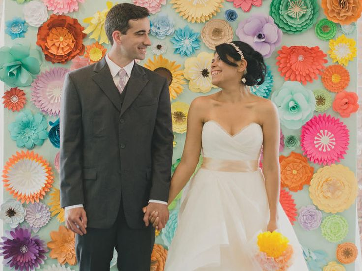 Vibrant paper flower wall at ceremony.  It is good to have a nice backdrop for people to pose in front of.
