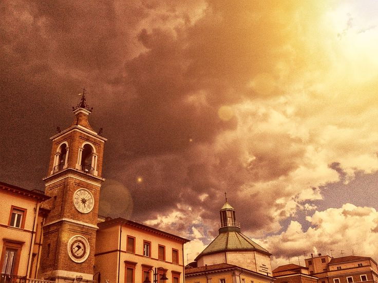 The Clock Tower and the Church of Saint Anthony in Rimini's Piazza Tre Martiri on a dramatically cloudy day.  http://www.visit-rimini.com/general-sightseeing/piazza-tre-martiri/