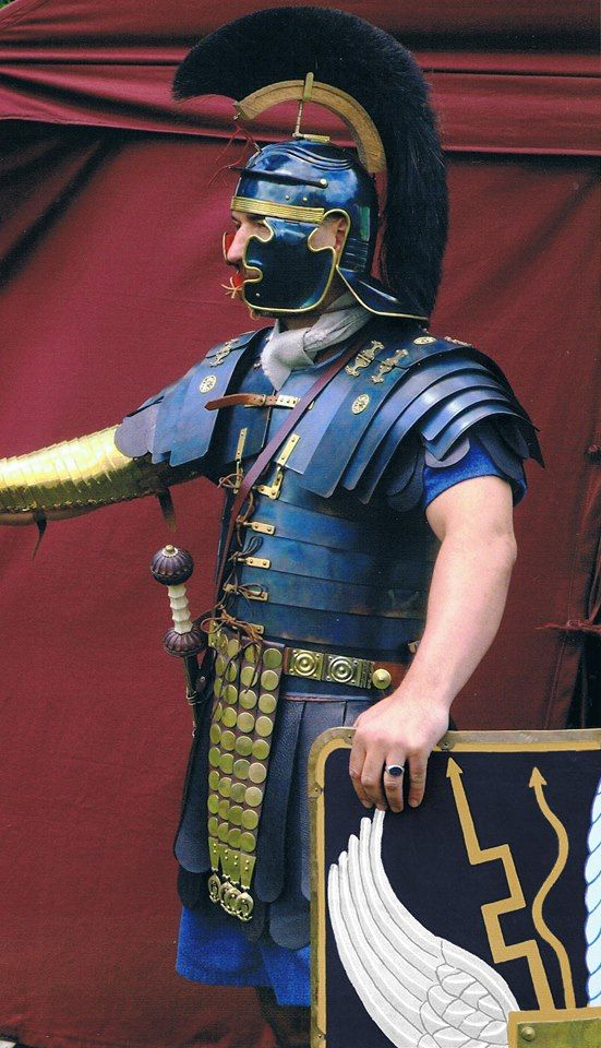 Roman optio reenactor wearing a blued and blackened Gallic C helmet and Lorica Segmentata of the Corbridge B type. He also wears a Manica of cupric alloy on his right arm, a defense adopted to deflect the Dacian Falx. His belt shows that he is a soldier of the Roman army, and only a soldier or retired soldier could wear one.