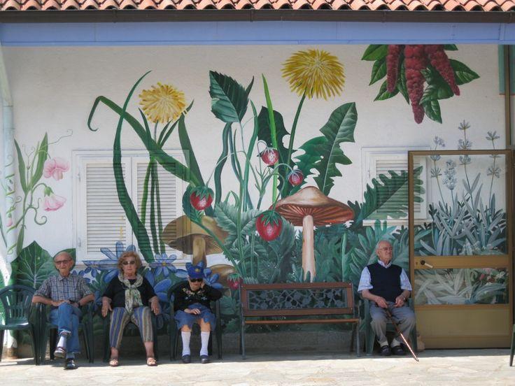 Senior Residents Sit Under A Typical Garden Mural.