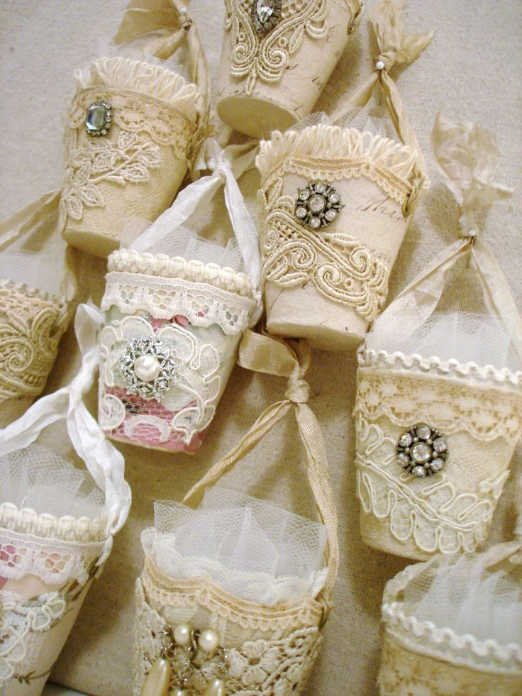 Altered peat pots, covered in beautiful lace and/or fabric, accented with more lace pieces; adorned in the front with a fragment of vintage jewelry; scrunched seam binding hanger