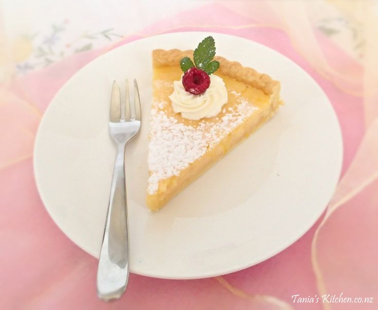 A sweet shortcrust pastry tart shell with a baked custard lemon filling. A beautiful dessert with whipped cream and berries, very summery.