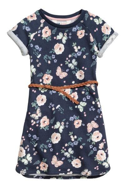 Een jurk van lichte joggingstof met een geprint dessin. De jurk heeft korte mouwen met een vastgestikte omslag en een afneembare, gevlochten riem van imitat