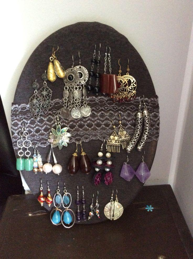 Bacheca porta orecchini realizzata con cornice in legno e calza autoreggente.