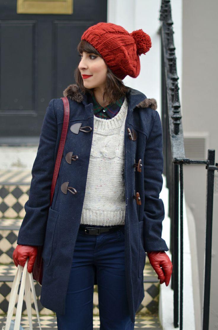 ネイビーのダッフルコートは中に着るインナーを白のケーブルニットにするとおしゃれ。ほどよいカジュアルさとメンズライクな雰囲気が素敵です。赤のニット帽とレザー手袋の組み合わせも素敵。