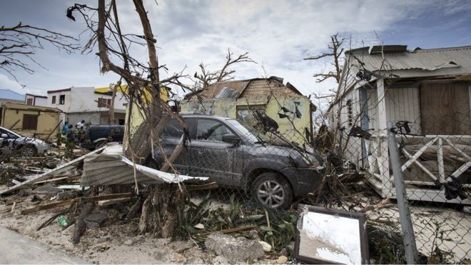 Image shows damaged homes and cars