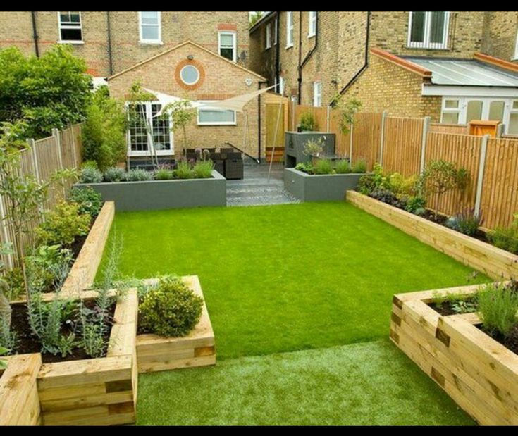 Multi sized raised flower beds along the length of the astro turf and decking.