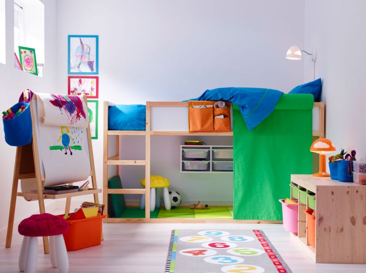 A colorful children's room with a loft bed in solid pine with space underneath for drawing and reading. Combined with low storage in solid pine with plastic boxes in pink, green and orange.