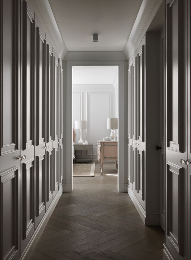Deeply molded closet doors line the hallway to the master bedroom. This luxurious Swiss chalet has been completely redesigned by the renowned interior designer Kelly Hoppen