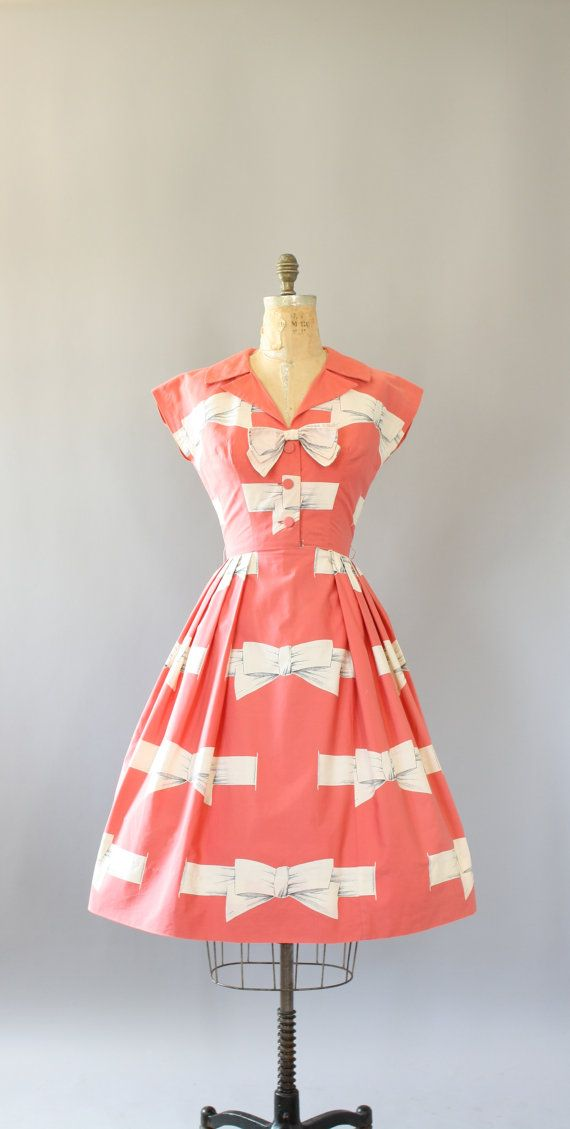 Vintage 50s AMAZING bubblegum pink cotton dress with white bow print. Cute white bow at neckline fastens with snap button. Buttons up in