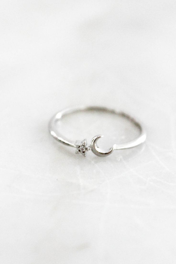 This silver high-polish ring is complete with a thin band and a half moon and star design on the front. Approximately a size 6. One size.