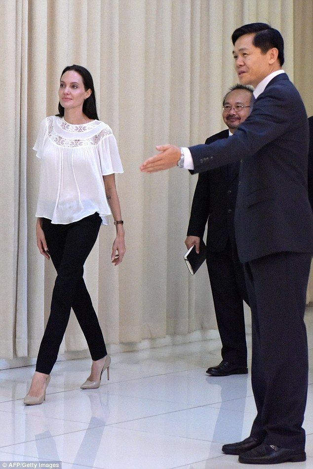 Ushered in: The 40-year-old actress and humanitarian was met by Cambodian politicians...