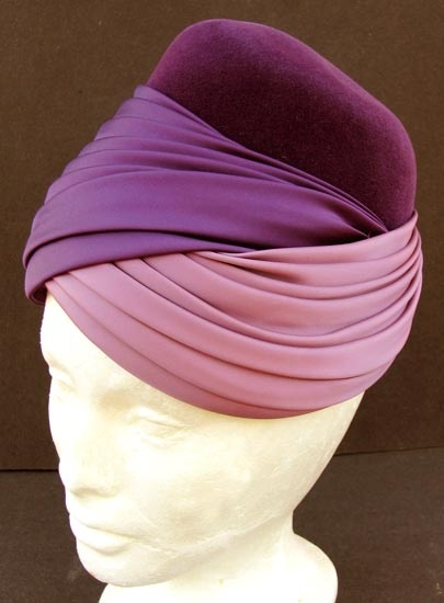 Elsa Schiaparelli's purple felt and satin turban. While most obviously famed for her more controversial pieces, throughout the 1930s and 40s Schiaparelli created incredibly elegant and sculptural headwear. Her skill as a milliner is particularly apparent during this time, with designs ranging from chic straw cocktail hats to silk turbans.