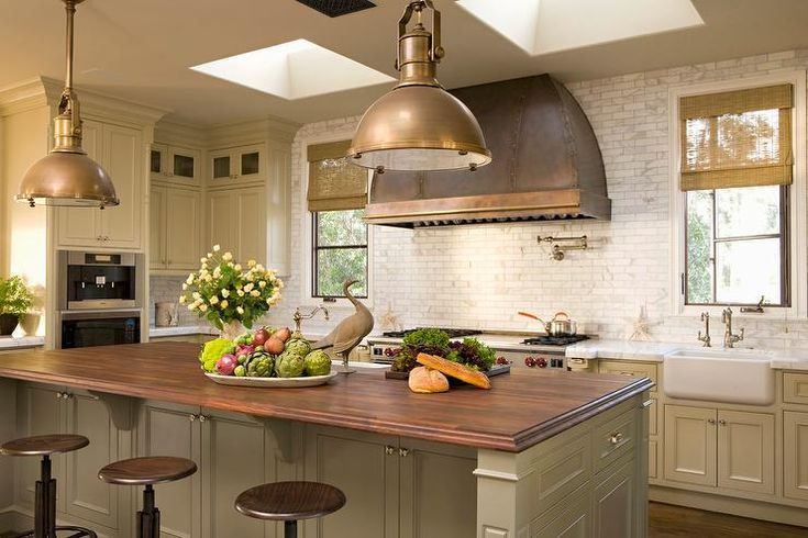 This stunning country kitchen in shades of brown features industrial swivel counter stools positioned facing a khaki kitchen island accented with a beveled stained wood countertop lit by Country Industrial Pendants.