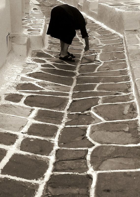 A Greek Yiayia is painting the alleyway, Chora, Mykonos Island, Greece * At work, focus, b/w